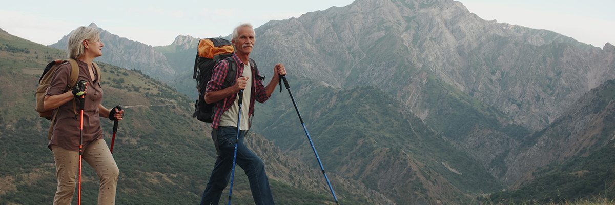 older man and woman hiking through utah mountains
