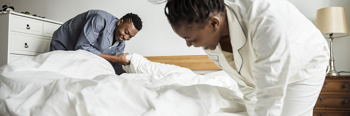 family making bed in luxury townhome